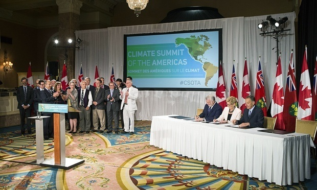 Fellow signatories applaud as Kathleen Wynne signs a declaration alongside Vermont's Governor Peter Shumlin, right, and Quebec's premier, Philippe Couillard, center left, at the Climate Summit of the Americas meeting in Toronto on 9 July.